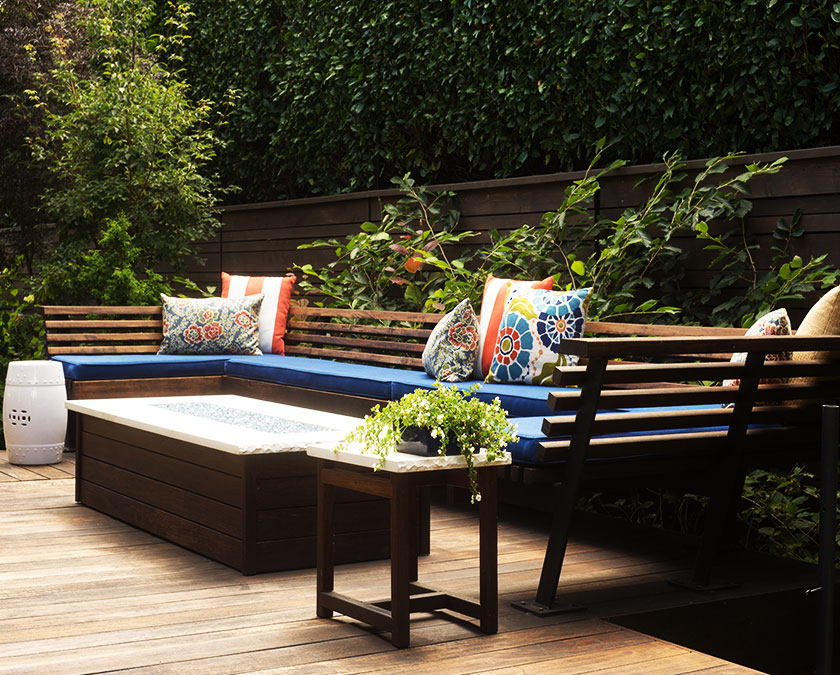 Composite deck with wooden bench and table, blue seat pillows, and lush greenery around.