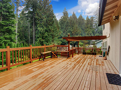 Composite deck with wooden railing, small wooden bench on the side and wood cover, surrounded by tall pine trees.