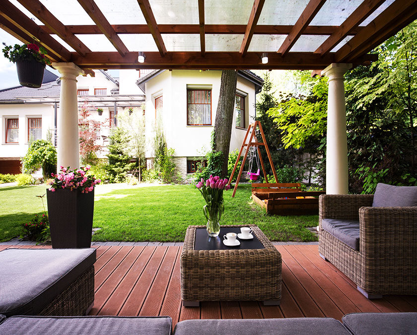 Small composite deck, with wooden cover, dark gray couch, flowers, and white house in the background.