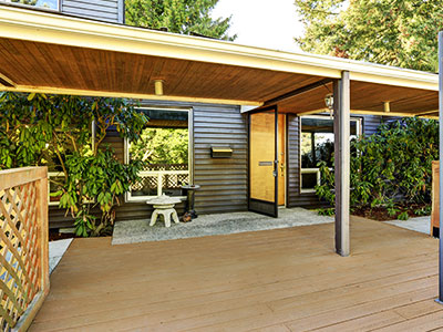 Dark beige stained deck with wooden fence, wooden cover, and a small tree near the house.