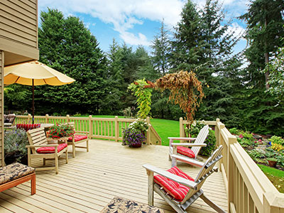 Light beige stained deck with wooden chairs, red chair seats, yellow shade umbrella, and pine trees in the background.