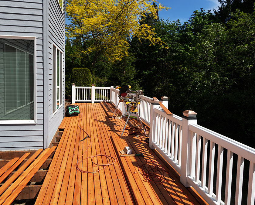 Deck construction view, with pressure treated pine deck boards, white wooden railing, connecting to a gray siding house.