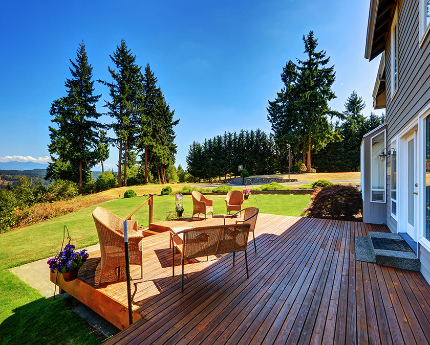 Wooden deck with relaxing, open space area, rattan chairs and table, and pine trees in the background.