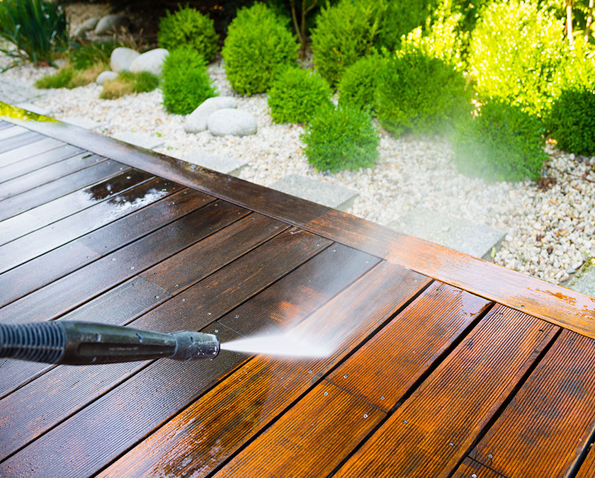 Power wash cleaning of wooden deck, with white sand and green shrubs in the background.